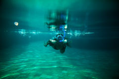 Girl swim underwater pool with snorkel Royalty Free Stock Photography