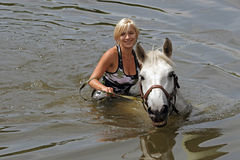 Girl swiming with her horse Royalty Free Stock Photo