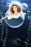 Girl Swiming Ocean. Adorable 7 year old girl in dress swimming under ocean swimming past treasure chest and bubbles royalty free illustration