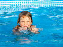 Girl swiming in a pool. Little girl palying in a swimming pool Royalty Free Stock Photo