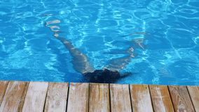 Girl swimmer floating under pure blue water in swimming-pool. In slow motion stock video footage