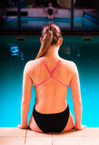 Girl swimmer muscular body  in swimsuit at poolside Royalty Free Stock Photo
