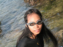 Girl with swimmers eyeglasses. Pirate girl in south of Philippines on the rock Royalty Free Stock Image
