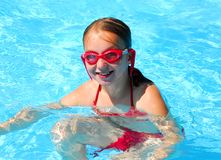 Girl swimming. Girl in red goggles in swimming pool Stock Image