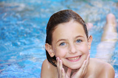 Girl swimming. A blue eyed girl lying in a swimming pool smiling at the camera with her hands cupped into her chin Royalty Free Stock Photography