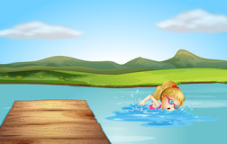 A girl swimming at the beach with a diving board Stock Photography