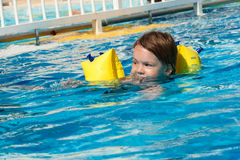 Girl swimming in blue water. Beauty girl with armlet swimming in swimming pool with blue water royalty free stock image