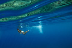 Girl swimming in blue water Stock Photo