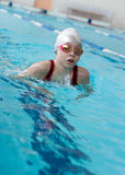 Girl swimming breaststroke in pool Royalty Free Stock Image