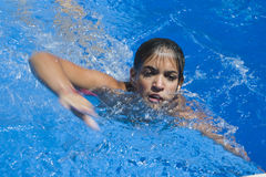 Girl swimming breaststroke in the pool,. Girl swimming in the pool breaststroke, reflects the movement and effort Swimmer Stock Images