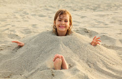Girl after swimming is buried in sand on beach Stock Images