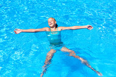 Girl in swimming circle relaxes in pool Stock Images