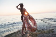 A beautiful girl walks the sea with a big circle. stock photography