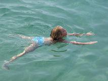 Girl swimming in crystal clear sea stock photo
