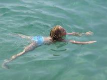 Girl swimming in crystal clear sea. Little girl swimming in crystal clear sea stock photo