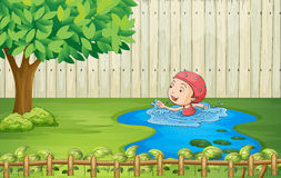 A girl swimming inside the fence Stock Image