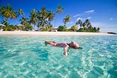 Girl swimming in lagoon. Girl floating and sunbathing on board in tropical lagoon Stock Image