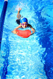 Girl Swimming. A little preteen girl wearing swim suit and swim gear in the water of the public pool. Shallow depth of field. Copy space Royalty Free Stock Images