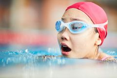 Girl swimming. Little swimmer in swim-cap and goggles breathing over water while swimming stock images