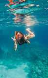 Girl in swimming mask dive underwater near coral reef. Showing victory sign royalty free stock photography
