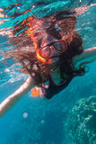 Girl in swimming mask diving in sea near coral reef Royalty Free Stock Image