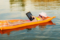 Girl on the swimming mattress with laptop Stock Photo