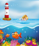 A girl swimming near the lighthouse Stock Images