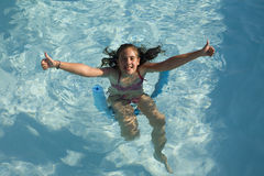 Girl in a swimming pool. Young girl having fun in a swimming pool and with thumbs up Stock Images
