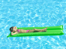 Girl in the swimming pool. Sunbathing Royalty Free Stock Images