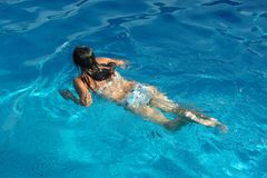 Girl swimming in pool royalty free stock images