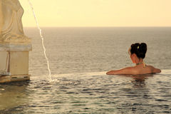 Girl Swimming In A Pool. Face beautiful ocean view at sunset Royalty Free Stock Photos