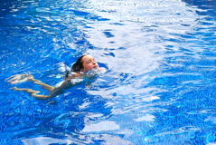Girl swimming in a pool. A white girl swimming in a pool and her head is above the water Stock Photos