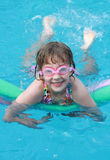 Girl Swimming in Pool. A little girl wears goggles while swimming in the pool Stock Images