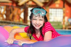 Girl in swimming pool. Young girl relaxing on an inflatable in a swimming pool Stock Images
