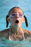 Girl swimming in the pool. Wearing swimming goggles taking a breath Stock Image
