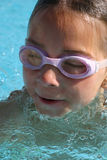 Girl swimming in the pool. Wearing swimming goggles Stock Photos