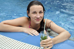 Girl in the swimming pool. With cocktail Stock Photo