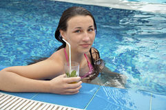 Girl in the swimming pool. With cocktail Royalty Free Stock Photos