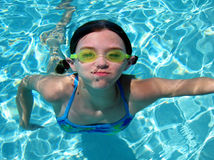 Girl in swimming pool. A girl holds her breath as she swims underwater in a pool royalty free stock photo