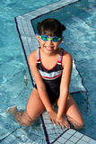 Girl at swimming pool. Girl with swimming costume sitting at swimming pool Stock Photography