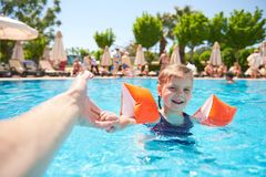 Girl swimming in the pool in armlets on a hot summer day. Royalty Free Stock Photos