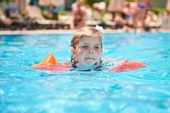 Girl swimming in the pool in armlets on a hot summer day. Stock Images