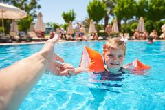 Girl swimming in the pool in armlets on a hot summer day. Royalty Free Stock Image