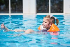 Girl swimming in the pool in armlets on a hot summer day. Stock Photo