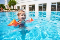 Girl swimming in the pool in armlets on a hot summer day. Stock Photos