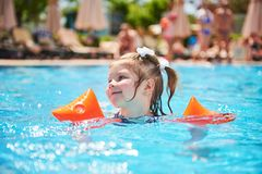 Girl swimming in the pool in armlets on a hot summer day. Royalty Free Stock Images