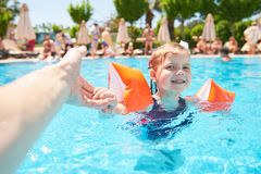 Girl swimming in the pool in armlets on a hot summer day. Royalty Free Stock Photo