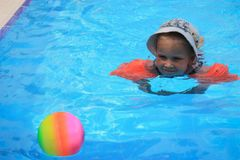 Girl swimming in a pool with a ball Stock Images