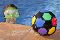 Girl is the swimming pool with color ball Royalty Free Stock Photography