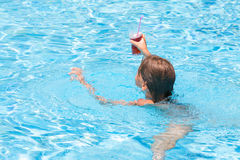 Girl swimming in the pool with a drink Royalty Free Stock Photos